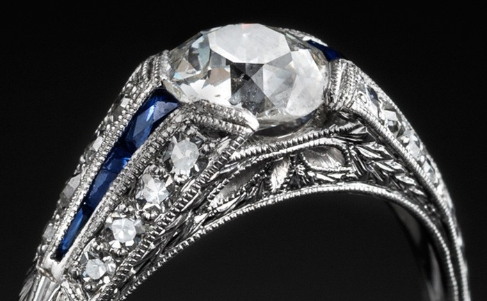 Detail of An Art Deco solitaire diamond ring with diamond and calibre cut sapphire shoulders