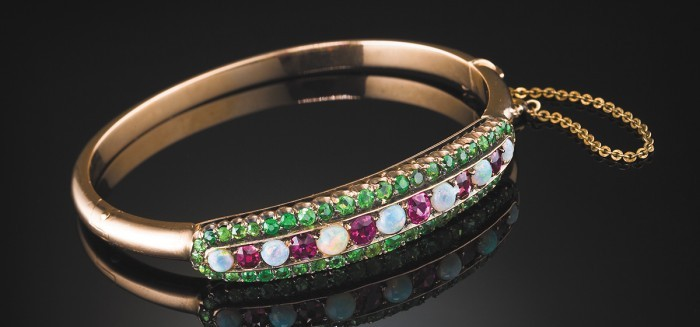 An antique ruby, opal and demantoid garnet pink gold hinged bangle