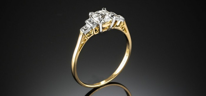 A late Art Deco diamond gold and platinum ring with stepped shoulders