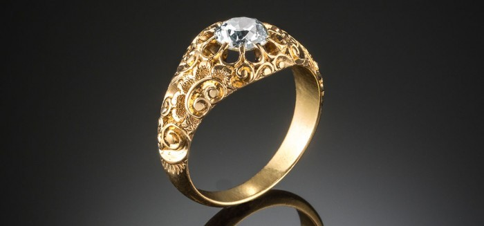 An antique gold and solitaire diamond ring
