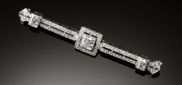 An Art Deco diamond brooch featuring three square emerald cut diamonds