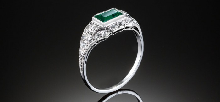 An Art Deco step cut emerald and diamond ring