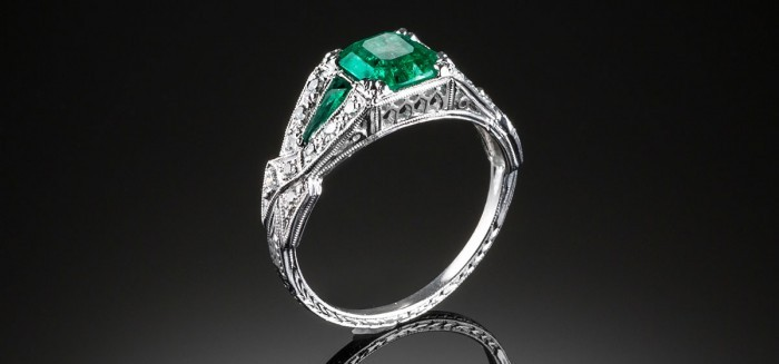 An Art Deco diamond and emerald ring with emerald shoulders