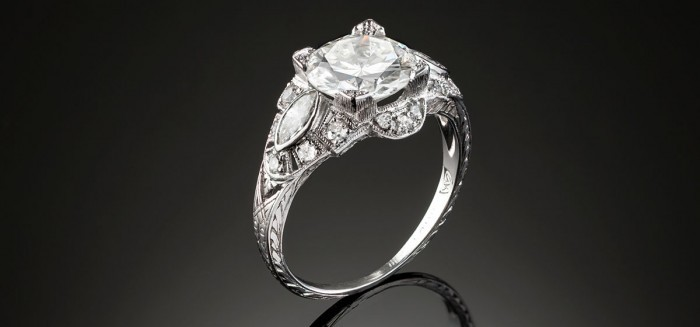 An Art Deco solitaire diamond ring with marquis and small diamond set shoulders