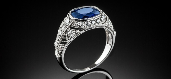 A PLATINUM ART DECO RING WITH A CUSHION SHAPE SAPPHIRE AND TRANSITION CUT DIAMONDS