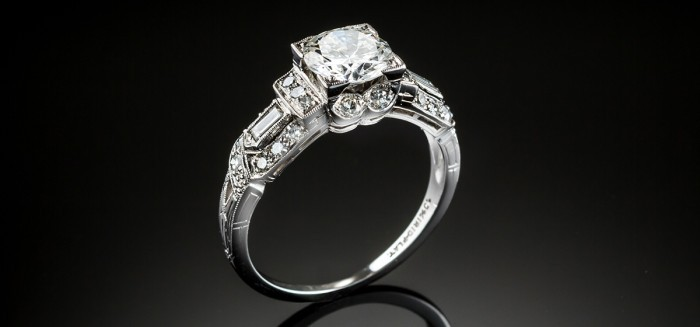 An Art Deco solitaire diamond ring with baguette and smaller diamond shoulders