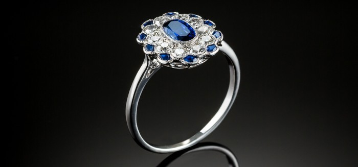 AN ART DECO SAPPHIRE AND DIAMOND RING WITH A DIAMOND AND SAPPHIRE BORDER