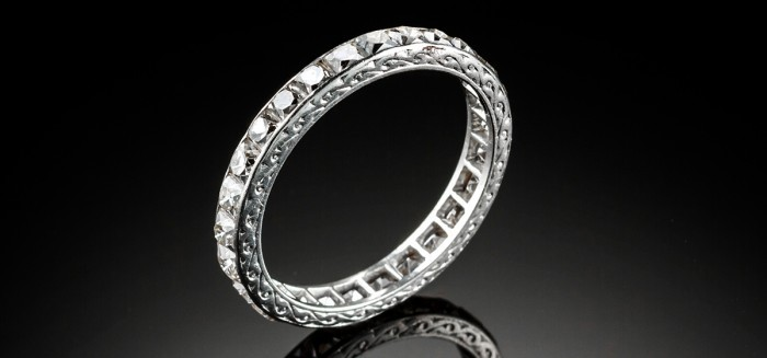 AN ART DECO PLATINUM AND FRENCH CUT DIAMOND ETERNITY RING
