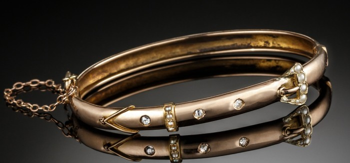 An Early Twentieth Century narrow hinged gold bangle with seed pearls and diamonds