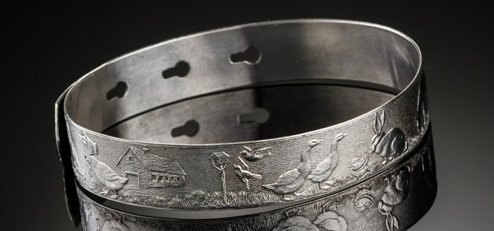 A 1940S STERLING SILVER CHILD'S BANGLE FINELY DECORATED WITH NURSERY RHYME SCENES