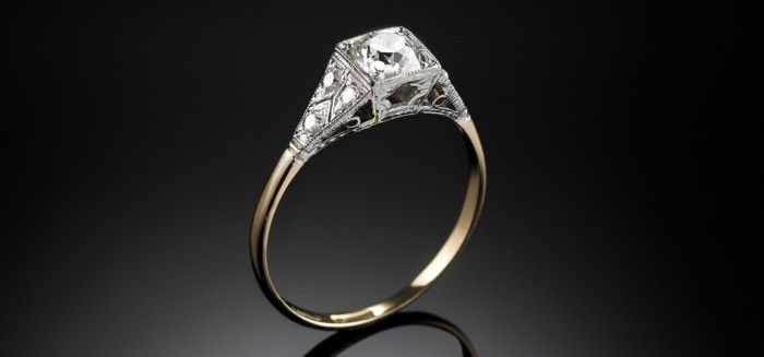 An Art Deco yellow gold and platinum solitaire diamond ring with diamond shoulders