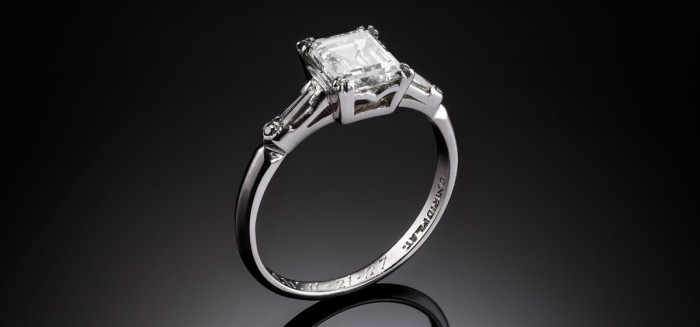 An Art Deco platinum/iridium ring, emerald cut diamond and baguette shoulders
