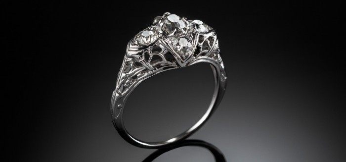 A platinum French Art Deco ring, the old European cut diamond solitaire surrounded by a further four