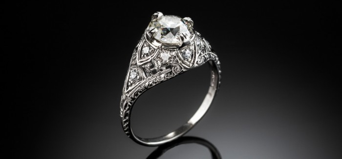An Edwardian platinum and solitaire diamond ring in a diamond embellished domed mount
