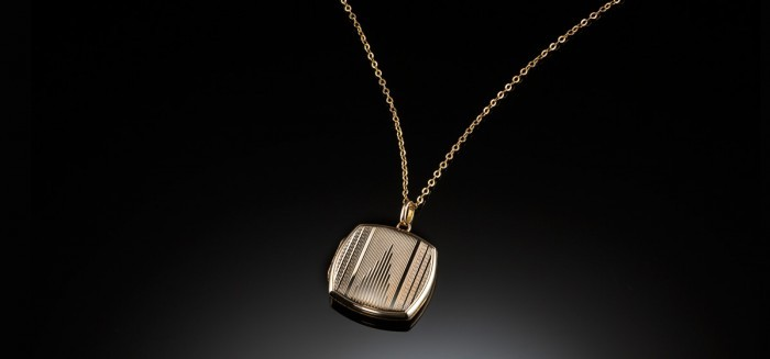 An Antique gold locket with later Art Deco engraving
