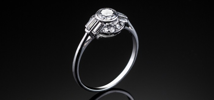 An Art Deco diamond and platinum ring contrasting curved and linear geometric elements
